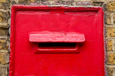 a traditional red post box in a wall.  photo