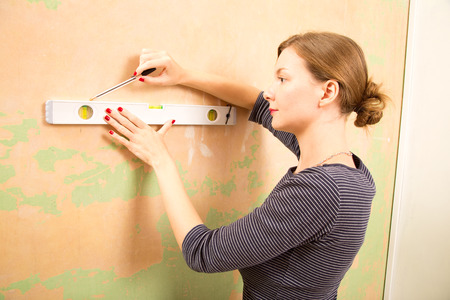 young woman using a spirit level.  photo