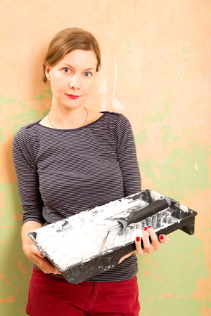 redecorating: woman holding a paint tray and roller.