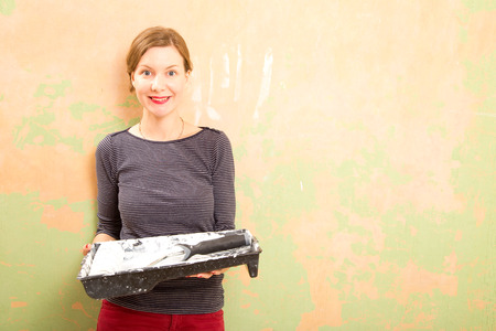 woman holding a paint tray and roller.  photo