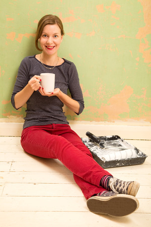 redecorating: happy woman drinking tea while decorating the house. Stock Photo