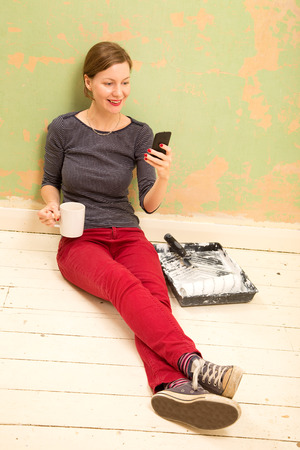 redecorating: young woman having a break from painting