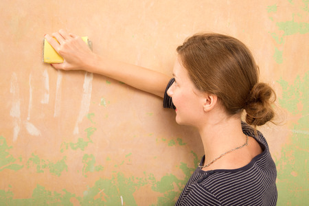 sanding block: young woman sanding wall Stock Photo