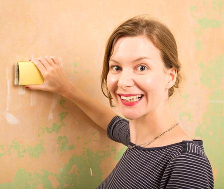 sanding block: young woman sanding wall Stock Photo