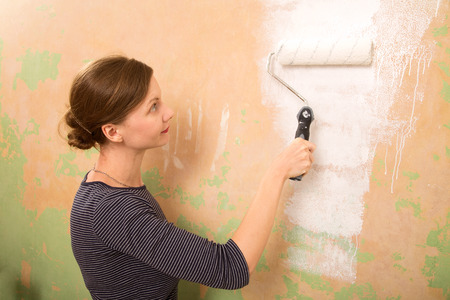 redecorating: young woman painting the wall
