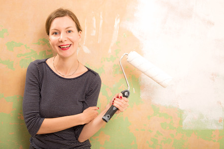 young woman painting the wall photo