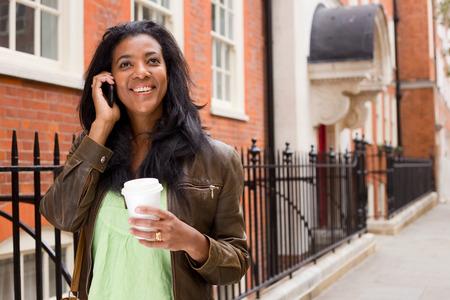 beautiful woman walking down the street talking on the phone.  photo