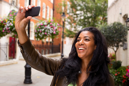 african american woman taking a selfie with her phone.  Stock Photo