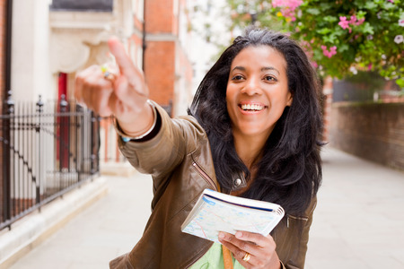 young woman with map pointing photo