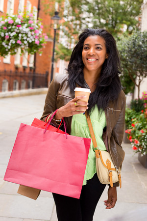 young woman with shopping bags and a take away coffee photo