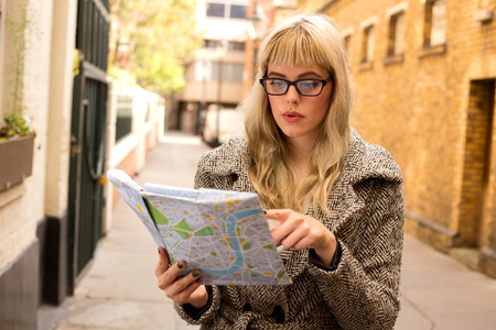 disoriented: woman reading map Stock Photo