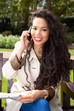 young woman talking on the phone with newspaper. photo