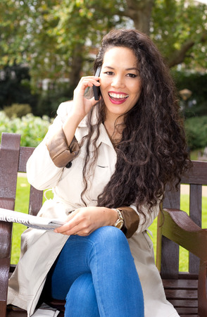 young woman talking on the phone with paper. photo