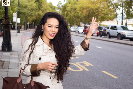hailing: young woman hailing a taxi