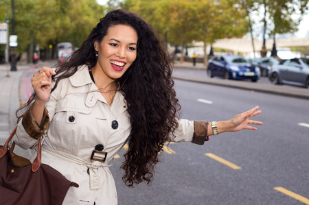 young woman hailing a cab photo
