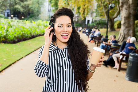 young woman listening to music in the park with a coffee. photo