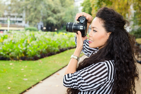passtime: young woman taking photos in the park.