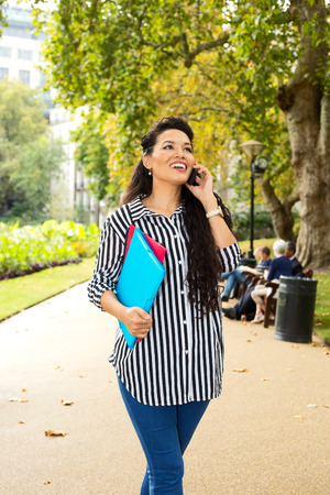 young woman talking on the phone holding folders. photo
