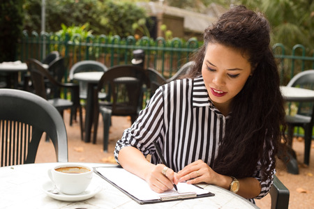 young woman writing on a clipboard with a coffee. photo