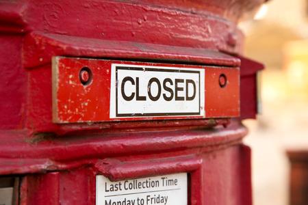 a shut red british letter box. photo