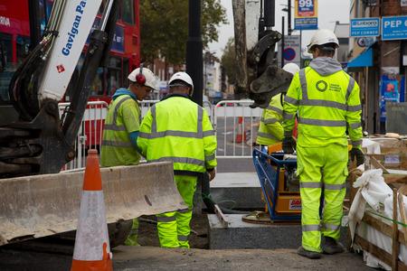 schlagbaum: LONDON - 15. Oktober: Unbekannte Arbeiter mit einem sprobst Vakuum-Steinmagnet von Turnpike Lane Station am 11. Oktober 2014 in London, England, UK. Sprobst ist der f�hrende europ�ische Hersteller von Steinf�rderer.