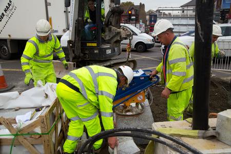 schlagbaum: LONDON - 15. Oktober: Unidentified Arbeiter mit einem sprobst Vakuumsteinmagneten von Turnpike Lane Station am 11. Oktober 2014 in London, England, UK. Sprobst ist der f�hrende europ�ische Hersteller von Steinf�rdertechnik.