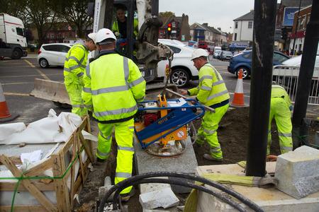 schlagbaum: LONDON - 15. Oktober: Unidentified Arbeiter mit einem sprobst Vakuumsteinmagneten von Turnpike Lane Station am 11. Oktober 2014 in London, England, UK. Sprobst ist der führende europäische Hersteller von Steinfördertechnik.