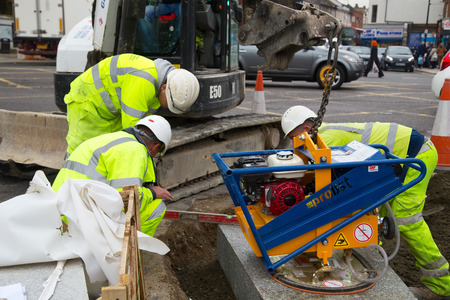 turnpike: LONDON - OCTOBER 15TH: Unidentified workman using a sprobst vacuum stone magnet by Turnpike lane station on October 11th, 2014 in London, England, UK. Sprobst is the leading european manufacturer of stone Handling Equipment.