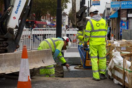 schlagbaum: LONDON - 15. Oktober: Unbekannte Arbeiter mit einem Vakuum-Steinmagnet sprobst von Turnpike Lane Station am 11. Oktober 2014 in London, England, UK. Sprobst ist der f�hrende europ�ische Hersteller von Steinf�rdertechnik.