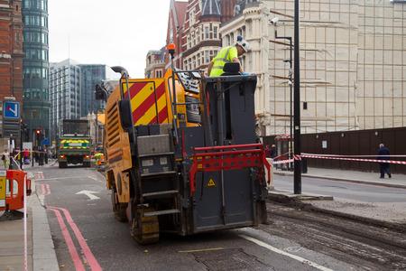 LONDEN - 18 oktober: Unidentified arbeider resurfacing een weg op 18 oktober 2014 in Londen, Engeland, UK. Out jaarlijkse wegvoorwaarde enquêtes de gemeenteraad carry's