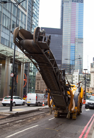 LONDEN - 18 OKTOBER: Niet geïdentificeerde werkman die een weg op 18 oktober, 2014 in Londen, Engeland, het UK weer opduiken. De gemeenteraad voert jaarlijkse road-condition surveys uit