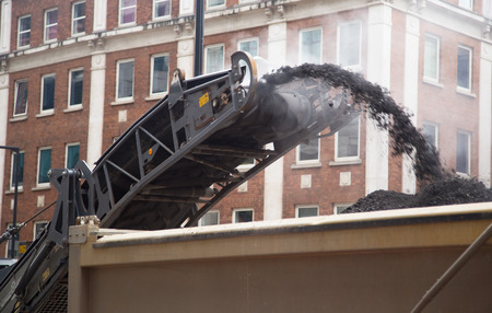 resurfacing: construction workers operate a cold milling machine.