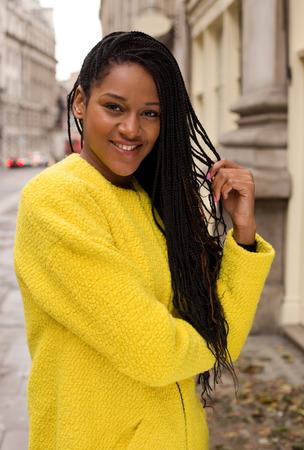 화려한 노란색 점퍼를 입고 아름 다운 아프리카 계 미국인 여자.
