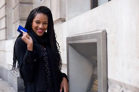 Een gelukkige jonge vrouw met een pinpas bij een pinautomaat. Stockfoto