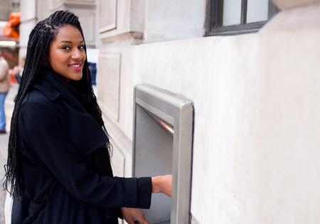 automatic transaction machine: una mujer joven y retirar dinero en efectivo