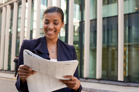reading newspaper: young business woman reading the newspaper