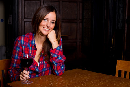 beautiful young woman enjoying a glass of wine photo