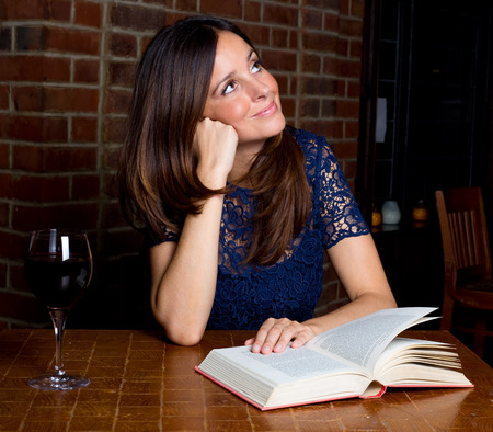 habbit: young woman looking thoughtful with a book and a glass of wine. Stock Photo