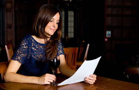 a young woman drinking wine and reading letter photo