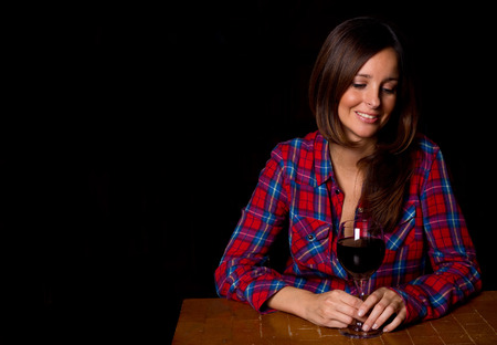 young woman drowns her sorrows with a glass of wine.