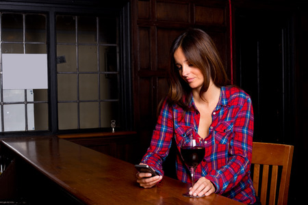 young woman sitting at bar enjoying wine. photo