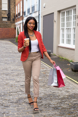 young woman with a coffee and shopping bags. photo