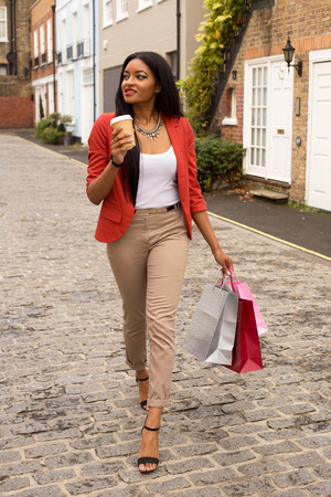 young woman with coffee and shopping bags photo