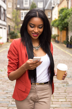 beautiful young woman reading a text message with a take away coffee photo