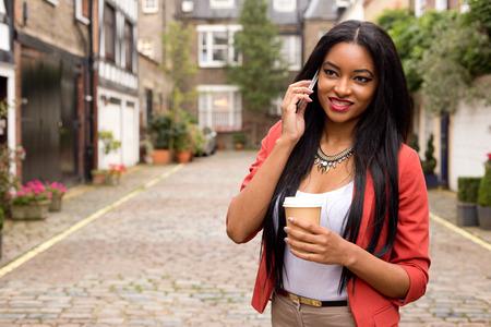 mujer tomando cafe: mujer joven en el teléfono con un café