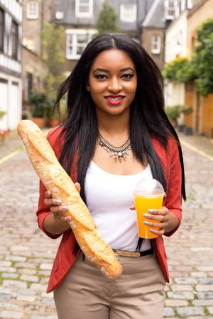 jugo de frutas: mujer que sostiene una barra de pan y jugo de fruta fresca