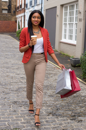 young woman with a coffee and shopping bags photo