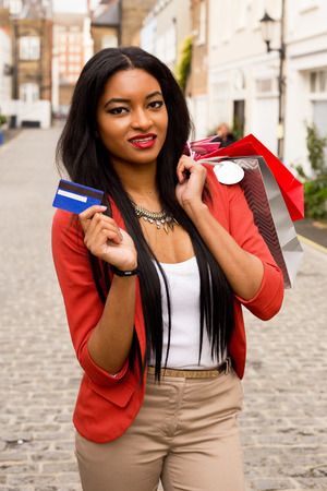 money bags: young woman showing a credit card holding shopping bags