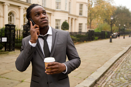 business man on the phone holding a coffee in the street photo