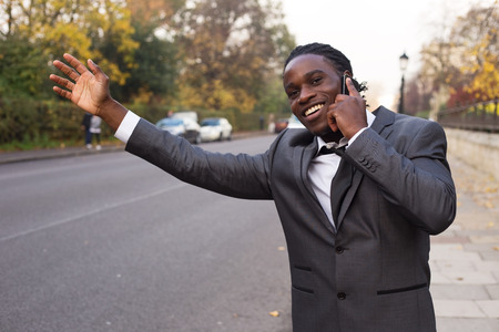 hailing: business man hailing a taxi on the phone. Stock Photo